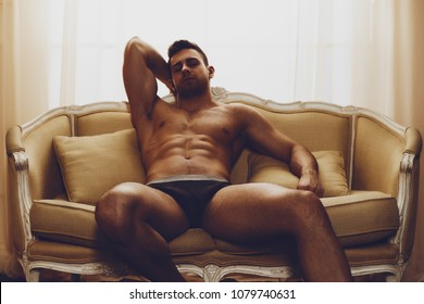 sexy and naked muscular young man posing on the sofa