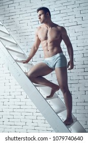 sexy and naked muscular young man Standing on stairs