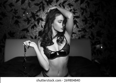Sexy naked woman with handcuffs in bedroom, black and white, bdsm
