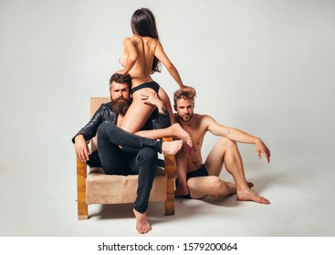 Sexy naked woman love in with two handsome bearded men. Group sex games at luxury chair. Full of desire men and woman menage going to have a sex. Three hot sex partners