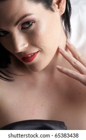 Sexy naked young caucasian adult woman with red lips, short black hair and a pierced eyebrow, covered in a dark satin sheet and sitting on a bed