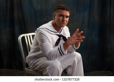 The sexy navy soldier poses for the camera.