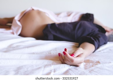 Sexy nude blonde woman lying in the bed in brown man's shirt