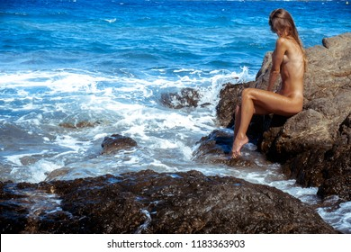 sexy nude girl on the rocks in the sea