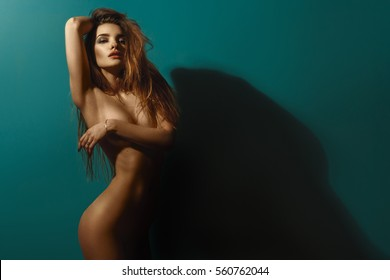 sexy nude girl standing near the wall covers hand chest and second hand raised above your head