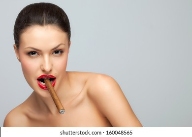 A sexy nude lady holding cigar in her mouth.