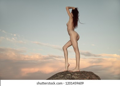 Sexy nude woman posing on the beach