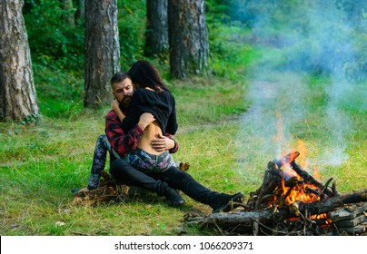 Sexy nude woman sits on man with beard. Couple full of desire going make love outdoor. Couple in love at picnic with fire in forest, trees on background, defocused. Love and sex concept.