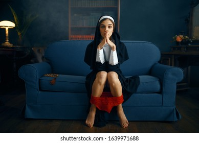 Sexy nun in cassock sitting with her panties down