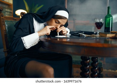 Sexy nun in a cassock sniffing cocaine