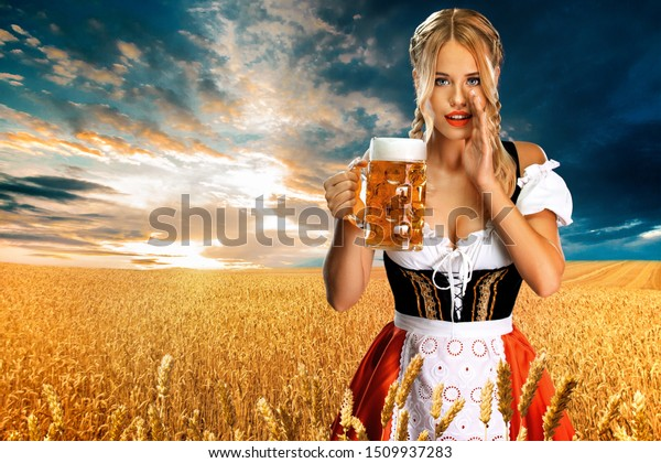Sexy oktoberfest girl waitress, wearing a traditional Bavarian or german dirndl, serving big beer mug with drink outdoor. . Woman have a secret.