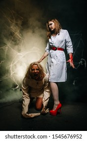sexy pair of doctor and patient at the Halloween party. a beautiful girl in stockings and a nurse's robe and a guy in a straitjacket with blood from his mouth.