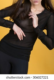 Sexy photo girl with sporty body in a black blouse on a yellow background.