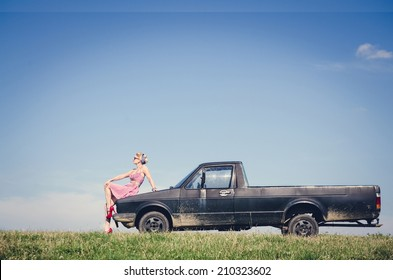 Sexy pin-up style girl sitting on the hood of retro pick up car