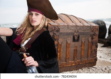 A sexy pirate woman poses with treasure and rum on the beach