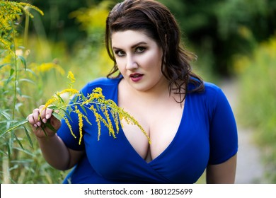 Sexy plus size fashion model in blue dress with a deep neckline outdoors, beautiful fat woman with big breasts in nature, body positive concept
