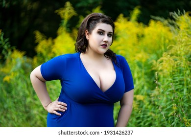 Sexy plus size model in blue dress with a deep neckline outdoors, beautiful fat woman with big breasts in nature, body positive concept
