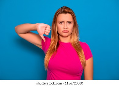 Sexy plus size model with long red hair in pink t-shirt on a blue background. Emotional portrait. She make thumbs down gesture