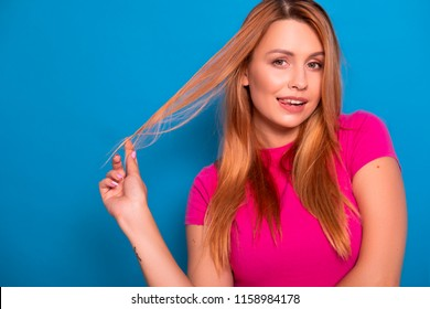 Sexy plus size model with long red hair in pink t-shirt on a blue background. Emotional portrait. She flirts, playing with her hair