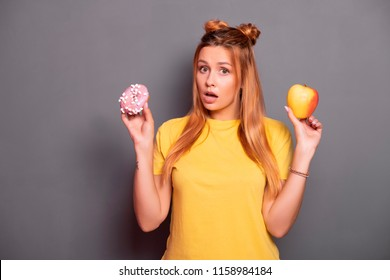 Sexy plus size model with long red hair in pink t-shirt on a neutral grey background. Emotional portrait. She shocked, amazed, tying to choose between good and bad food: apple or donut?
