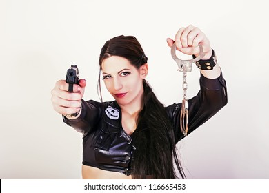 Sexy police woman holding a gun and handcuffs