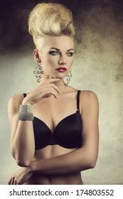 sexy portrait of charming young girl posing with aristocratic expression, creative hair-style and lingerie. Wearing black bra and glossy jewelleries
