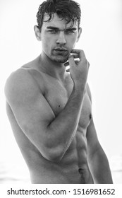 Sexy portrait of handsome wet topless male model with beautiful eyes looking into the camera. Black and White.
