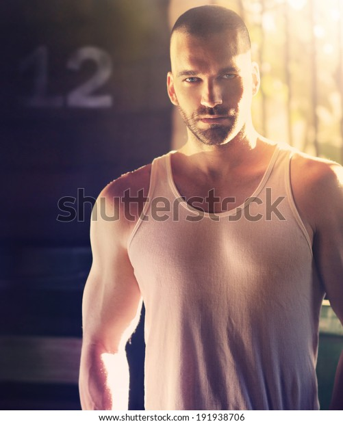 Sexy portrait of masculine man with shaved head in hard dramatic light and shadow