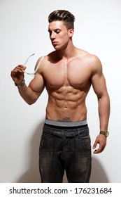 Sexy portrait of a very muscular shirtless male model against white wall in sensual pose . Fashion colors.