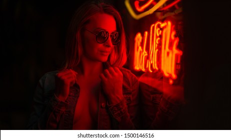 Sexy portrait of a young girl with an open bust in sunglasses and with in the night city, in the red light of neon lamps. Night clubs, parties, strip business, night life, business game. Banner