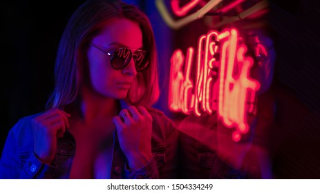 Sexy portrait of a young girl in sunglasses and with in the night city, with creative light on the background of neon lamps. Night clubs, parties, strip business, night life.