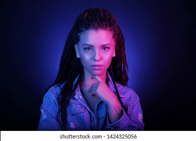 Sexy portrait of a young woman, in neon pink and blue light. Girl with dreadlocks in a nightclub, sexy turtleneck, radiant makeup with highlighter. Glitter skin. Clubber, night life concept