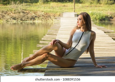 Sexy posing brunette woman in white swimwear over natural landscape. Horizontal shot.