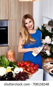 Sexy pretty beautiful woman with white teeth smile wear slim fit blue dress in the kitchen eats sweet tasty cake baking makeup diet right food cook chef housewife lady model culinary.