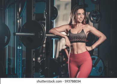 Sexy pretty caucasian fitness model on diet resting and working out in the gym. Girl execute exercise with barbell