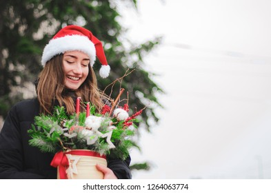 sexy pretty Christmas woman, brunette girl with holywood smile wearing santa hat holding xmas tree in her hand on a snowing street background. Christmas wreath. selective focus