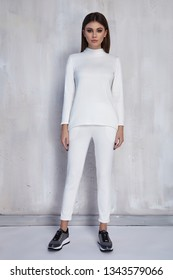 Sexy pretty fashion woman wear white casual sport suit trend clothes collection catalogue long brunette hair party style model pose bright make-up beautiful face dress code office accessory shoes.