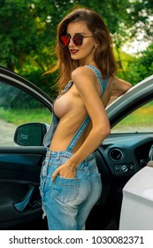 sexy pretty girl with big breasts posing nude near car in jeans dress