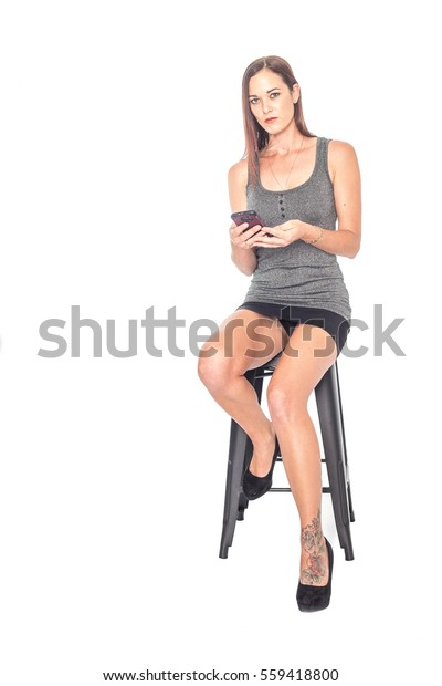 01ed8f787ea6 sexy Pretty girl looking at her phone,wearing short mini skirt sitting on a  Bar