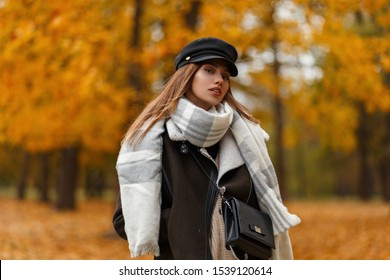 Sexy pretty young woman in a stylish hat in a brown jacket with a leather bag with a scarf posing on the background of trees with orange leaves in the park on a autumn day. Attractive girl outdoors.