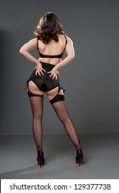 sexy rear view of retro model in black lingerie & seamed stockings