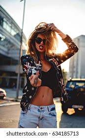 Sexy rebel girl showing middle finger while standing in the street
