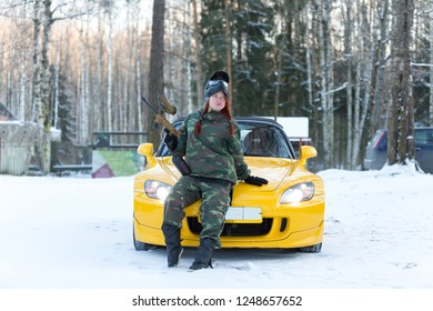 Sexy red hair girl in military uniform with paintball marker posing on sport car bonnet