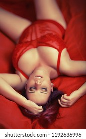 sexy red head girl with big breasts in red lingerie on bed