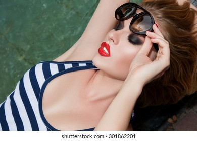 Sexy Red Lips. Beautiful girl with a Lipstick on her lips in Sun Glasses in Profile. Model at the Pool with Seductive Big Red Lips. Close-up Face Make-up, girl looks from under  sunglasses