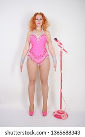 sexy red-haired caucasian girl in a pink bodysuit with tassels and  in fishnet pantyhose with rhinestone posing like a doll on a white background in Studio