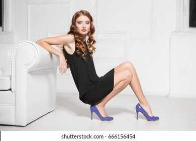Sexy red-haired woman posing near white sofa in the studio