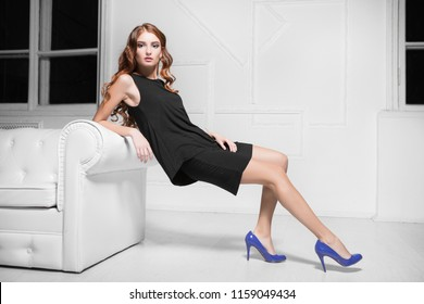 Sexy red-haired woman wearing black dress and blue shoes posing near white sofa