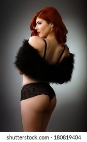 Sexy redhead woman in black lingerie isolated on gray background