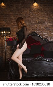 Sexy redhead woman in dark lace lingerie at vintage interior. Lady with fashionable figure, full hips, long legs